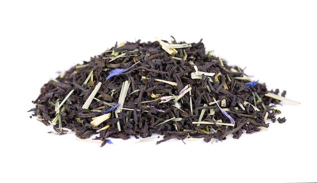 Czarna herbata cejlońska z płatkami trawy cytrynowej i chabru na białym tle.
