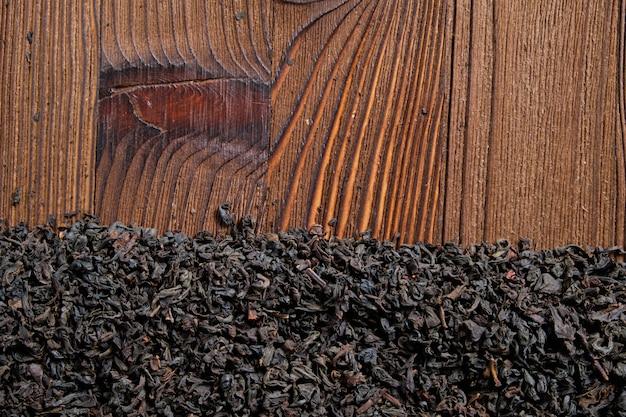 Czarna herbata na spalonym drewnianym tle. widok z góry. skopiuj miejsce