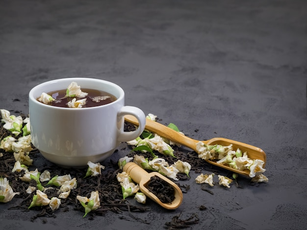 Czarna herbata w białej filiżance na czarnej teksturze
