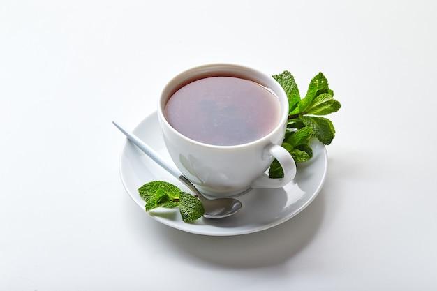 Czarna herbata w białej filiżance z listkami mięty łagodząca herbata antystresowa