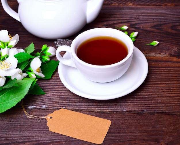 Czarna herbata w białej filiżance ze spodkiem