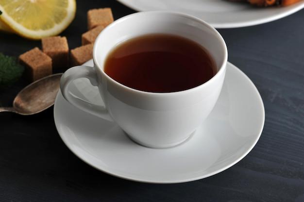Czarna herbata w kubku na spodku, cytryna i mięta