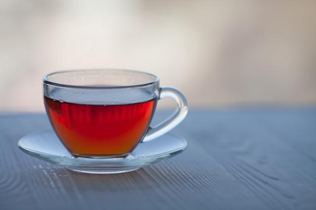Czarna herbata w szklanej filiżance na niewyraźne tło.