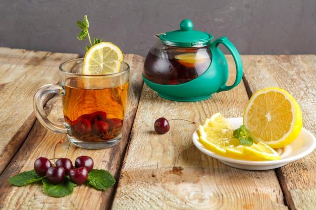 Czarna herbata w szklanej filiżance z wiśniami miętowymi i cytryną na drewnianym stole obok świeżych wiśni i imbryka. poziome zdjęcie