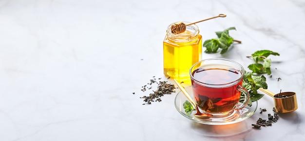 Czarna herbata w szklanym przezroczystym kubku z listkami mięty i miodem uspokajająca i rewitalizująca herbata antystresowa i relaksacyjna