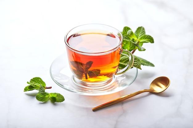 Czarna herbata w szklanym przezroczystym kubku z listkami mięty kojąca herbata antystresowa