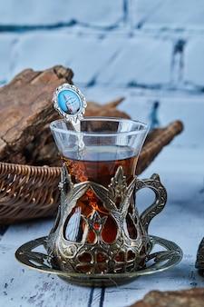 Czarna herbata w tradycyjnej szklanej filiżance i ciasteczka na niebieskim drewnianym stole