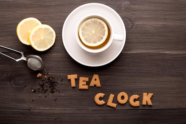 Czarna herbata z cytryną i ciastkami herbacianymi na drewnianym stole