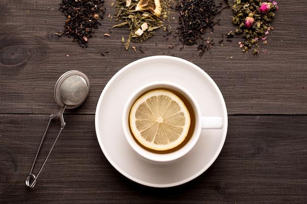 Czarna herbata z cytryną i kilka widoków herbaty na drewnianym stole