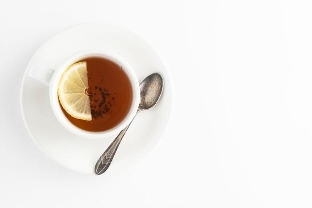 Czarna herbata z cytryną i miodem na białym tle. filiżanka gorącej herbaty na białym tle, widok z góry płaskie leżał. leżał płasko. napój jesień, jesień lub zima. copyspace.