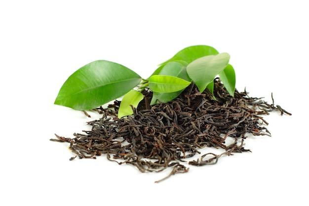 Czarna herbata z zielonym liściem na białym tle