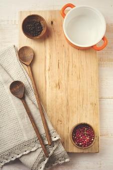 Czarna i czerwona papryka, ceramiczna patelnia, drewniany stojak, proste stare łyżki i lniana serwetka na lampce. koncepcja akcesoriów kuchennych.