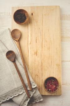 Czarna i czerwona papryka, drewniany stojak, proste stare łyżki i lniana serwetka na świetle. koncepcja akcesoriów kuchennych.