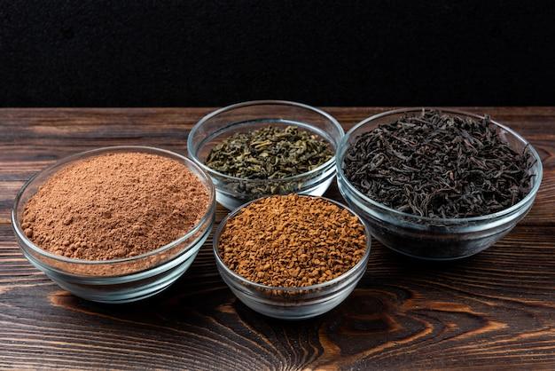 Czarna i zielona herbata, kakao i kawa na ciemnym tle drewnianych.