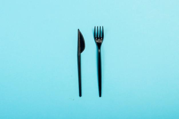 Czarna jednorazowa plastikowa zastawa stołowa i urządzenia do żywności. koncepcja plastiku, szkodliwe, zanieczyszczenie środowiska, zatrzymaj plastik. leżał płasko, widok z góry.