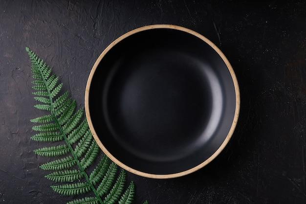 Czarna kamienna miska z liśćmi palmowymi na czarnym tle kopiowanie miejsca ciemne zdjęcie mockup