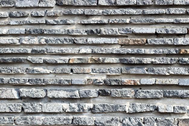 Czarna kamienna ściana do użytku w tle. stary kamienny mur. imitacja kamienia. kamień naturalny.