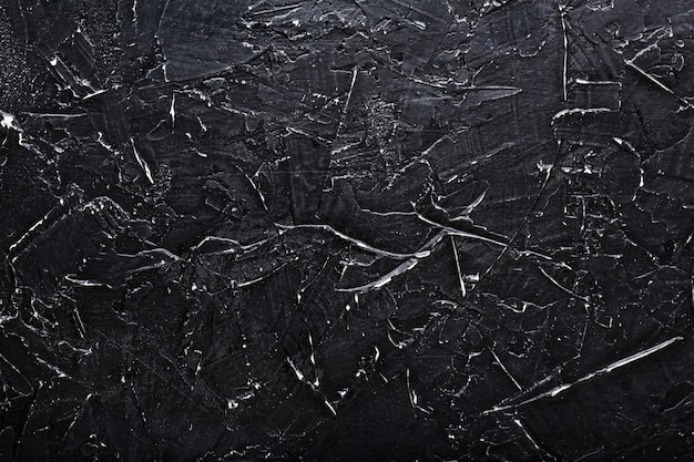 Czarna kamienna ściana tekstur z białymi zadrapaniami. pełny ekran jako