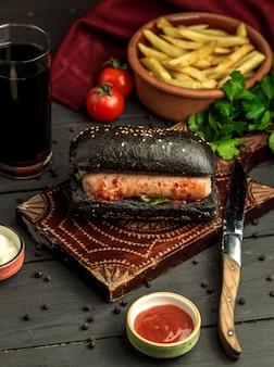 Czarna kanapka z kiełbasą i ogórkiem podana z frytkami