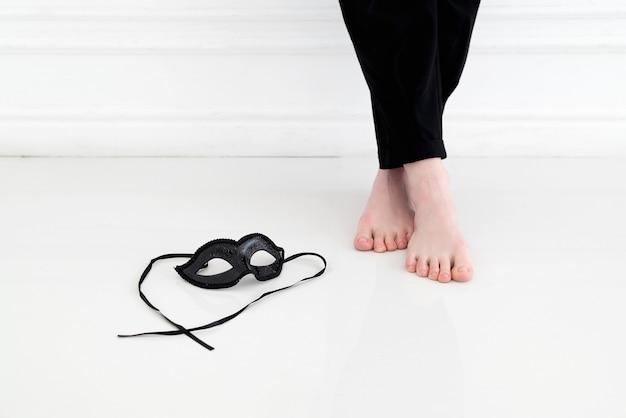 Czarna karnawałowa maska ze sznurowadłami leży na białej podłodze w pobliżu bosej stopy młodej kobiety w czarnych spodniach, która stoi przy białej ścianie
