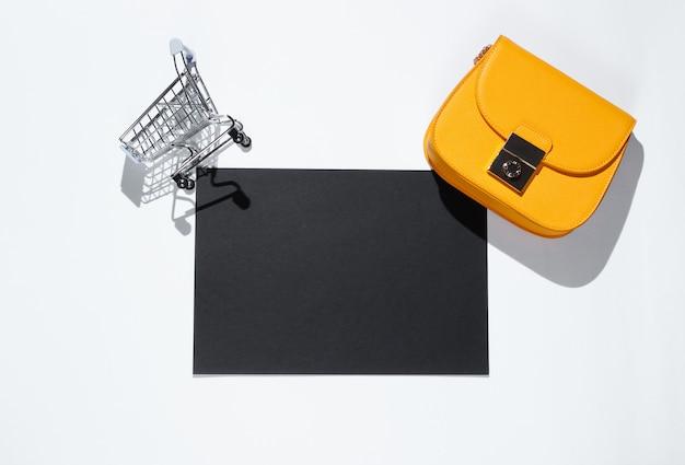 Czarna kartka papieru do kopiowania miejsca, mini wózek na zakupy, torba na szarym stole. kreatywny stolik na zakupy