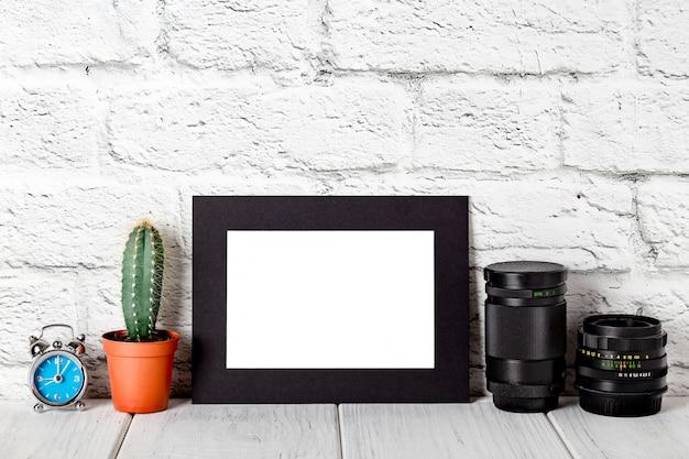 Czarna kartonowa ramka na biały stół przed murem. makieta przed murem. makieta