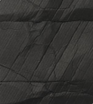 Czarna kartonowa tekstura z fałdami, pełna rama, wnętrze pudełka na perfumy, z bliska
