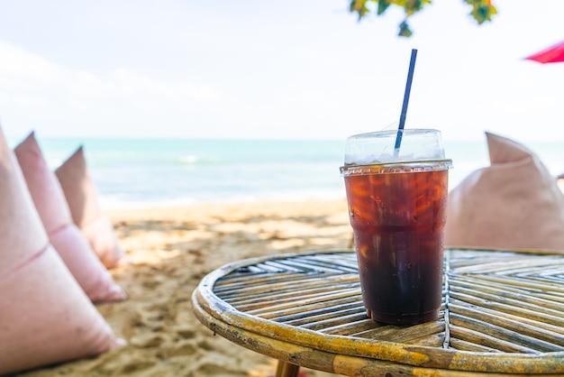 Czarna kawa americano szklanka z morzem w tle