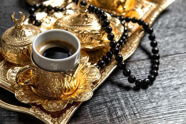 Czarna kawa arabska, złote ozdoby i różaniec. ramadan kareem