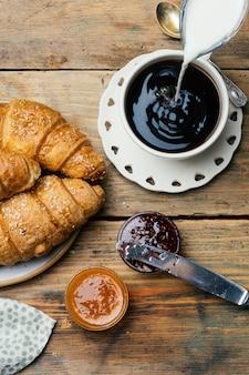 Czarna kawa i rogaliki z dżemem. typowe francuskie śniadanie (petit déjeuner)