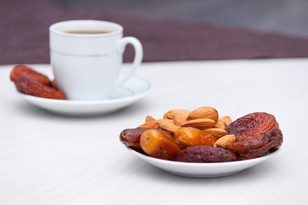 Czarna kawa i suszone owoce na białym tle