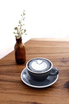 czarna kawa latte art w drewnianym stole