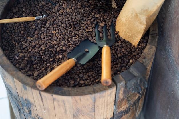 Czarna kawa palone ziarna kawy i mielona kawa w łyżki drewna i cynamonu