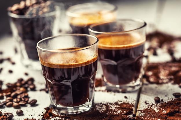 Czarna kawa po turecku w szklanych filiżankach i rozsypanych ziarnach kawy.