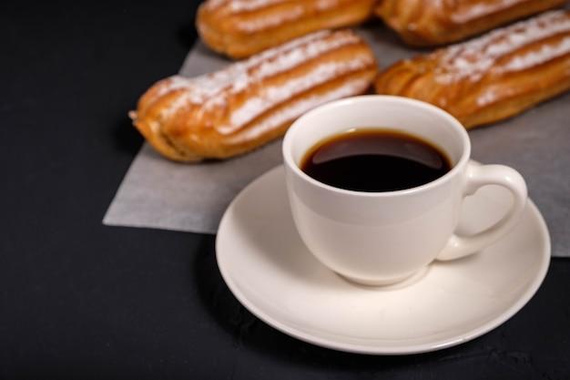 Czarna kawa w białej filiżance i eklerki ze śmietaną na ciemnym tle