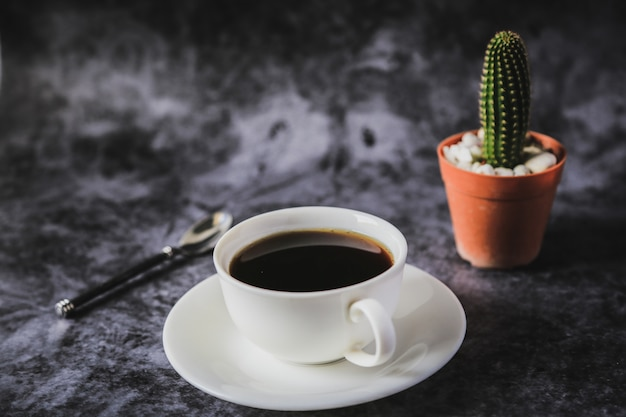 Czarna kawa w białej filiżance i kaktusie umieszczonym