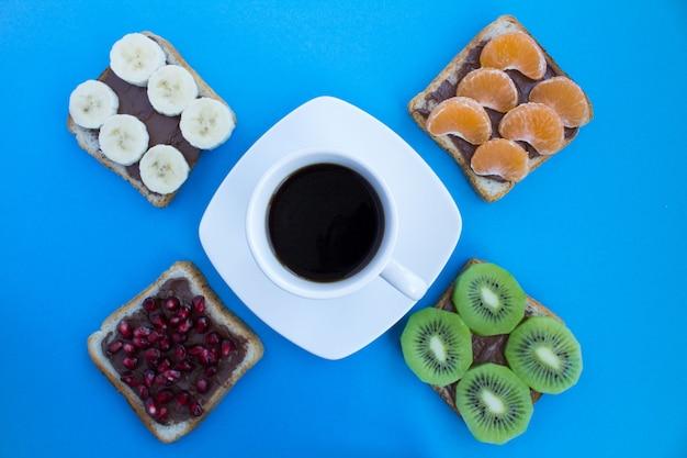 Czarna kawa w białej filiżance i kanapki z kremem czekoladowym i owocami na niebieskim tle.
