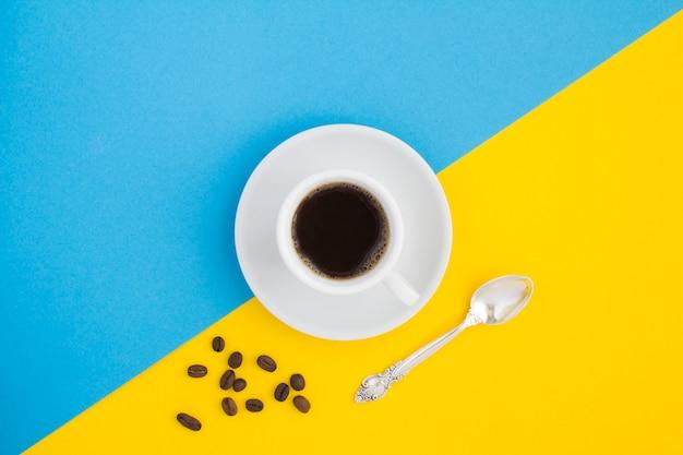 Czarna kawa w białej filiżance i kawa ziarnista w dwukolorowym.