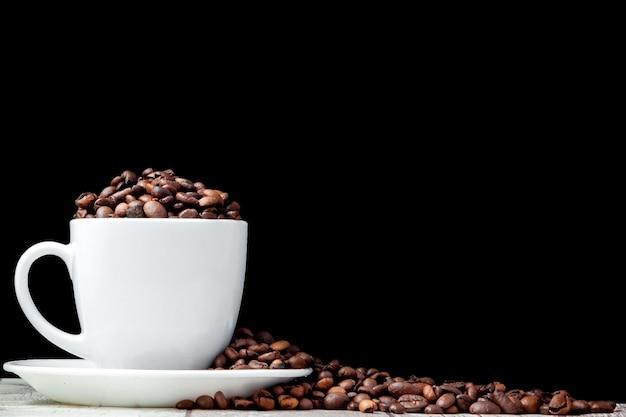 Czarna kawa w białej filiżance i kawowych fasolach na czarnym tle.