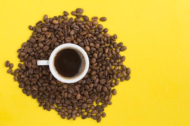Czarna kawa w białej filiżance i ziarna kawy na żółtej powierzchni