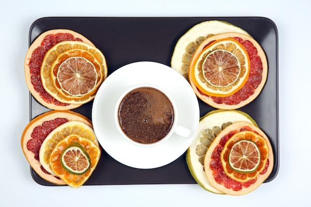 Czarna kawa w białej filiżance otoczona suszonymi owocami cytrusowymi