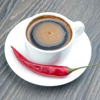 Czarna kawa w białej filiżance z czerwoną ostrą papryką na talerzu. pikantne jedzenie i mocny napój.