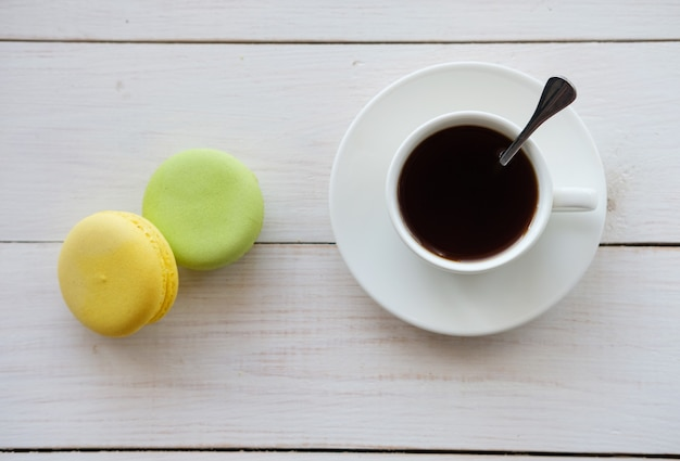 Czarna kawa w białych ciastach puchar i makaronik na białym drewnianym stole