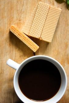 Czarna kawa w białym szkle i wafel umieszczony na drewnie.