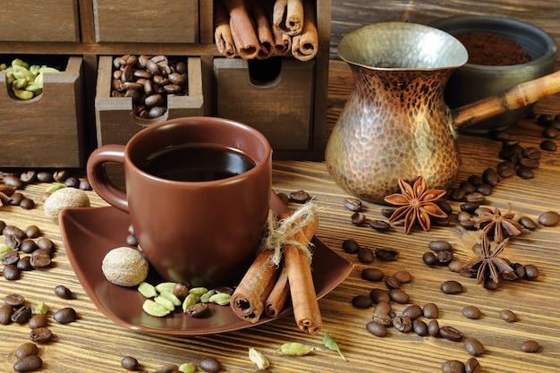 Czarna kawa w brązowy kubek i przyprawy na drewnianym stole