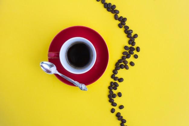 Czarna kawa w czerwonej filiżance i ziarna kawy na żółto