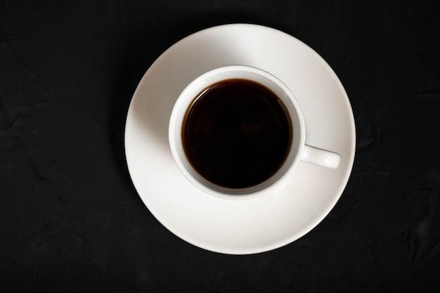 Czarna kawa w filiżance białej herbaty na ciemnej powierzchni
