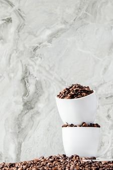 Czarna kawa w filiżance i kawowych fasolach na marmurowym tle.