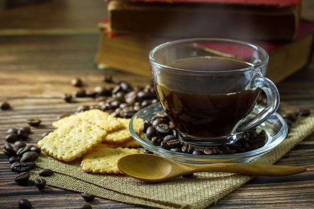 Czarna kawa w filiżance jasne szkło i ziarna kawy z krakersami i starej książki na drewnianym stole.