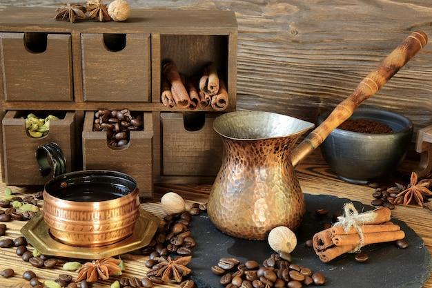 Czarna kawa w miedzianej filiżance i przyprawy na drewnianym stole